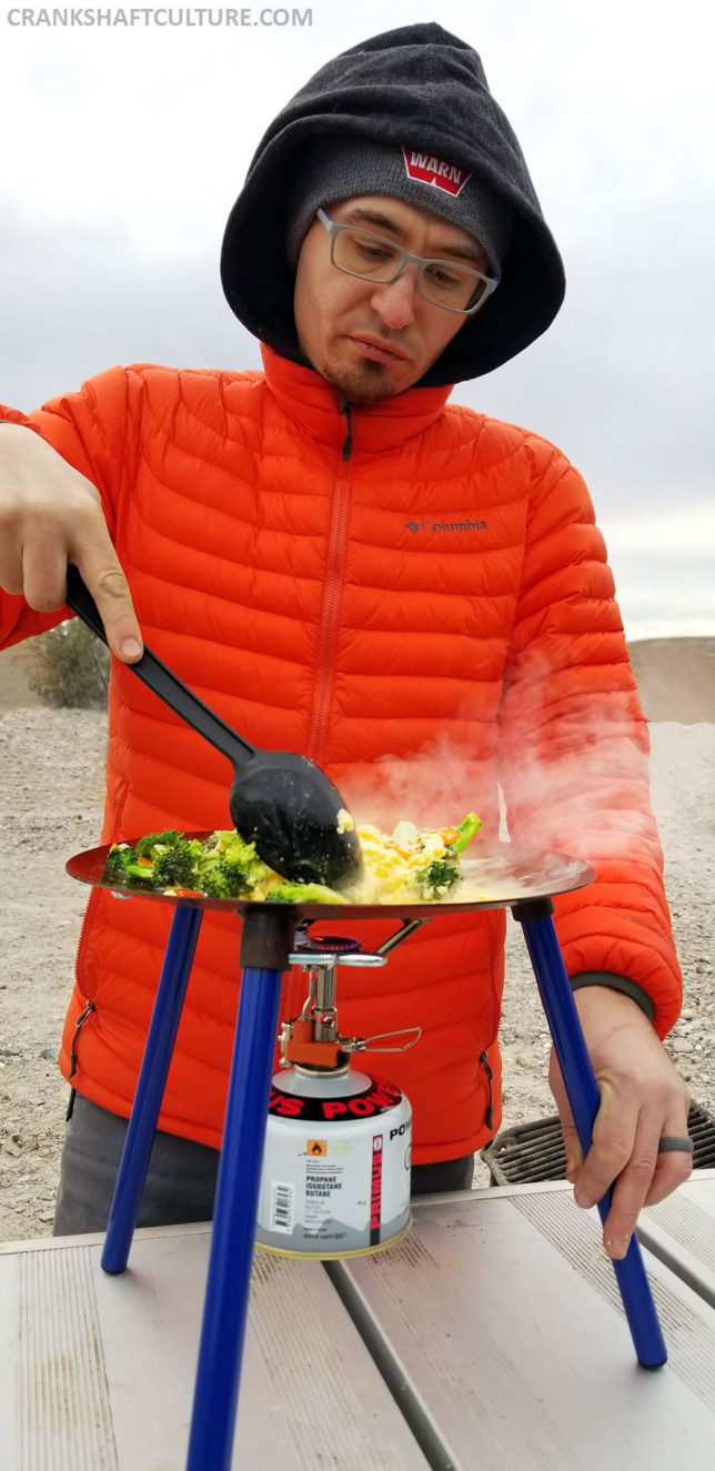 Andy using plastic utensils to cook on the Tembo Tusk Adventure Skottle.