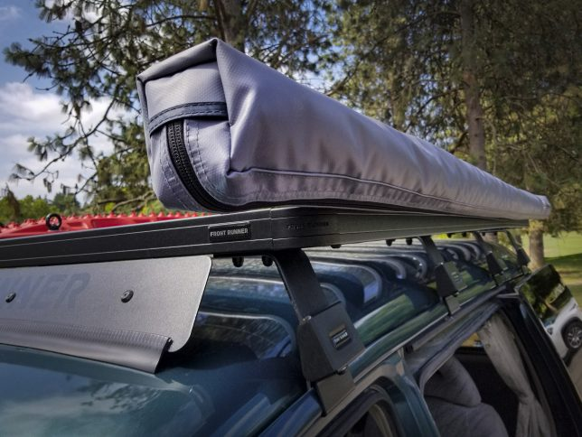 ARB814410 awning in closed position on black Front Runner rack