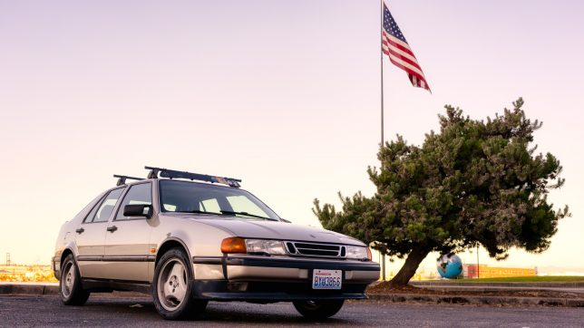 Saab 9000 with American flag at sunset.