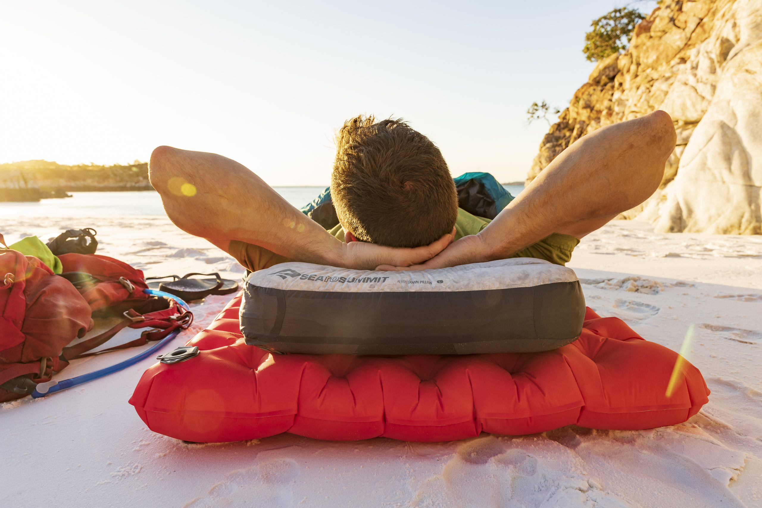 Sea to Summit offers all sorts of camp gear, including inflatable pillows and sleeping pads like the red pad and gray and white pillow shown here with a man laying on it.